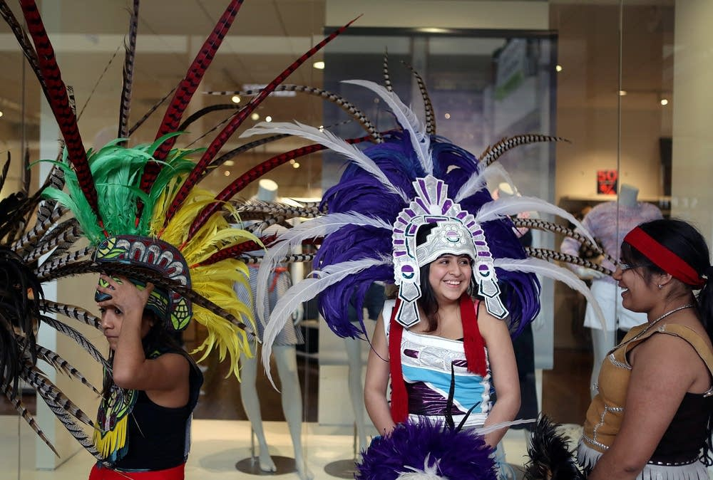 """Dressed in traditional, hand-made regalia, Joselin Navarro-Cano joked with Michelle Ochoa, right, as Jackie Gomez, left, and other members of the Kalpulli KetzalCoutlique dance group prepared to perform at Southdale Mall, April 18, 2015"" Photo and text courtesy of Jeffrey Thompson of MPR News"